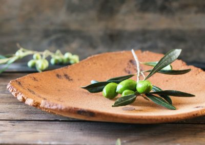 Green and black olive branch on clay plateover wooden table.